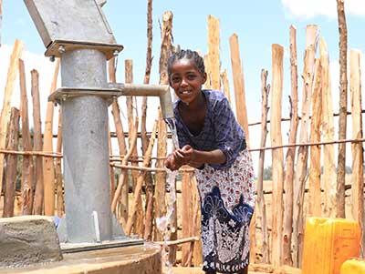 Junges Mädchen in Äthiopien pumpt Wasser aus einem sauberen Brunnen