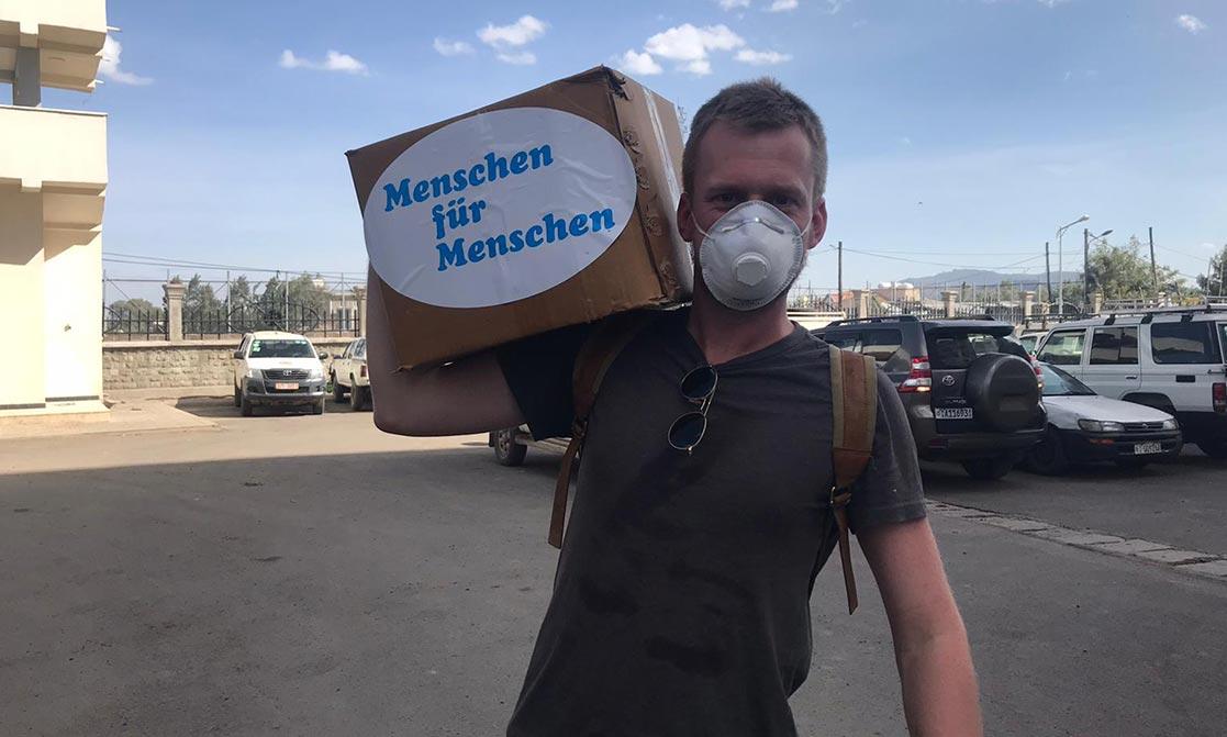 Ein Mann mit Mundschutz trägt eine Kiste.