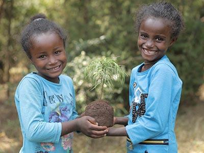 Zwei Mädchen in Äthiopien mit Baumsetzling in der Hand
