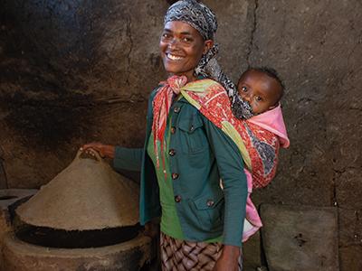 Frau mit Baby vor einem Ofen