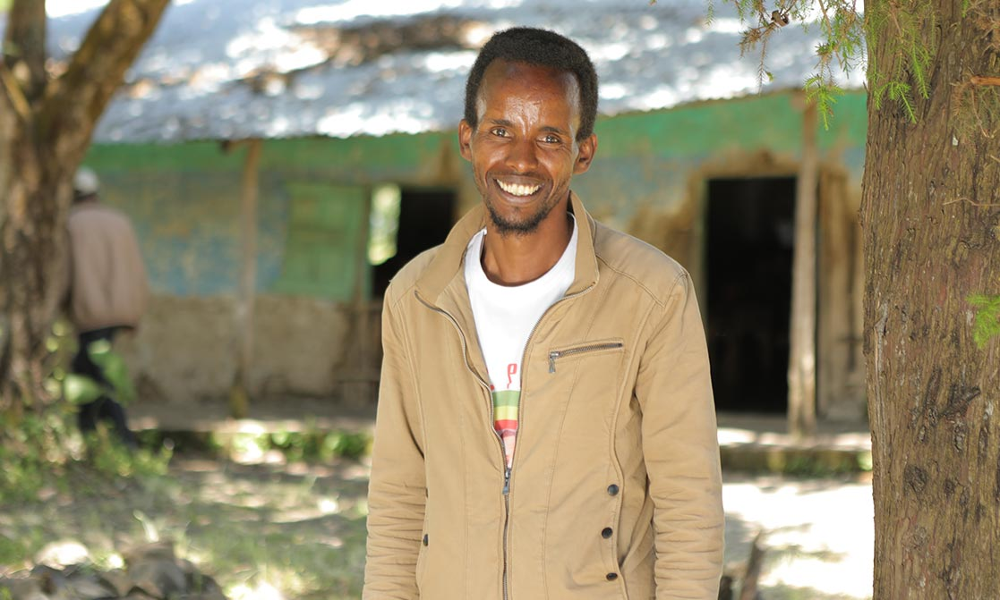 Ein lächelnder Äthiopier steht vor einem verfallenen Schulgebäude.