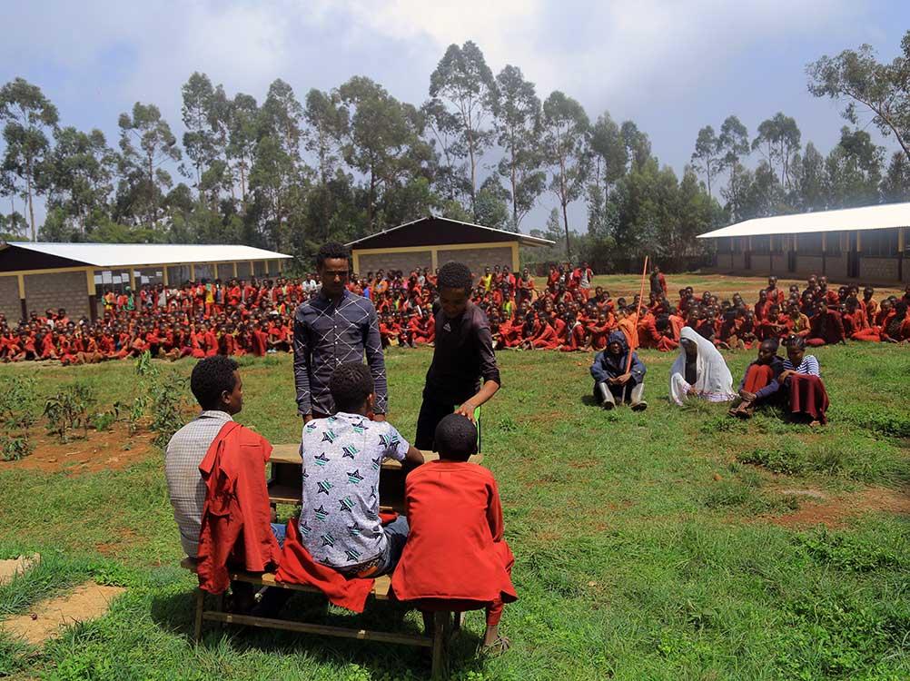 SchülerInnen sitzen auf einer Wiese