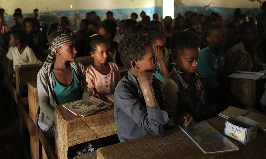 Kinder sitzen in einem dunklen Klassenzimmer.