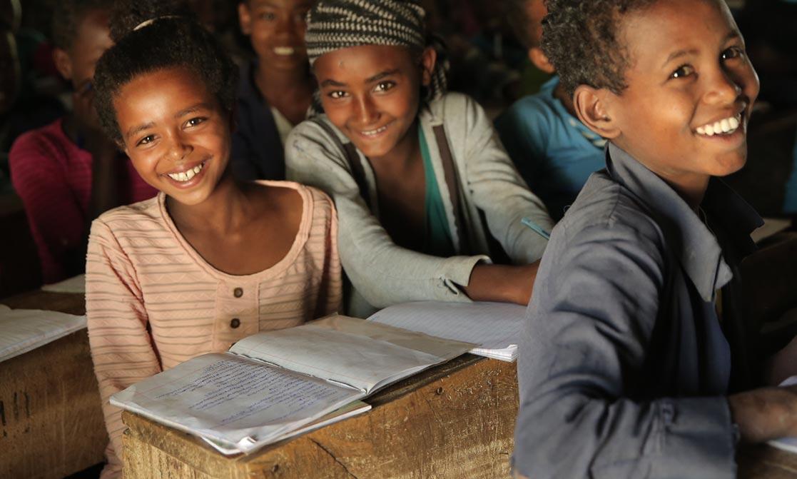 Zwei Mädchen sitzen in einem dunklen Klassenzimmer und lächeln in die Kamera