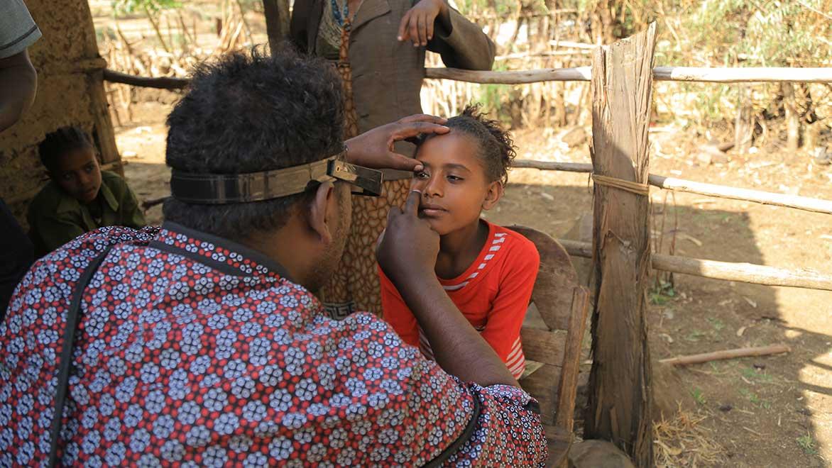 Ein Mann untersucht die Augen eines Mädchens.