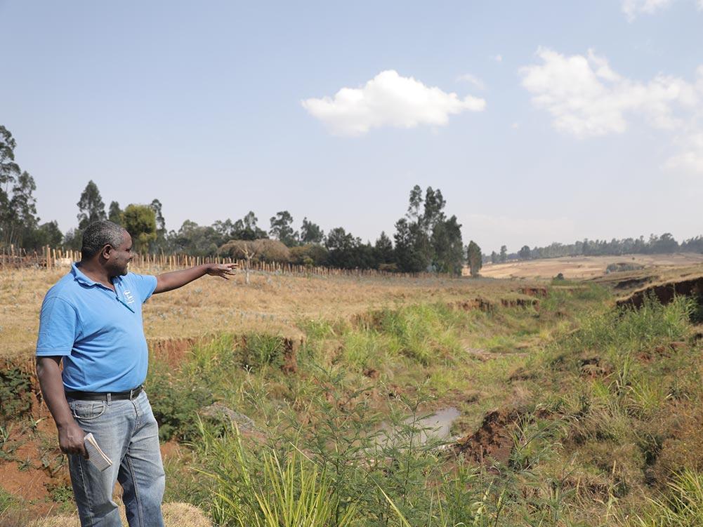 Ein Mann zeigt auf einen Erosionsgraben.