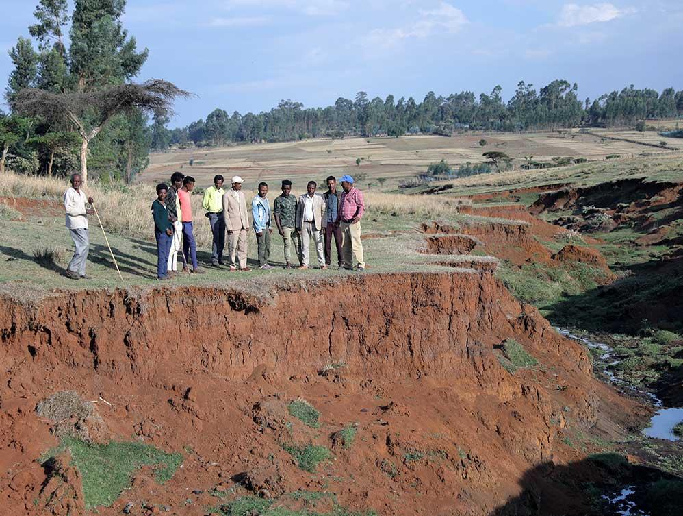 Männer stehen vor einem tiefen Erosionsgraben.