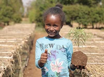 Äthiopisches Mädchen mit Baumsetzling in der Hand