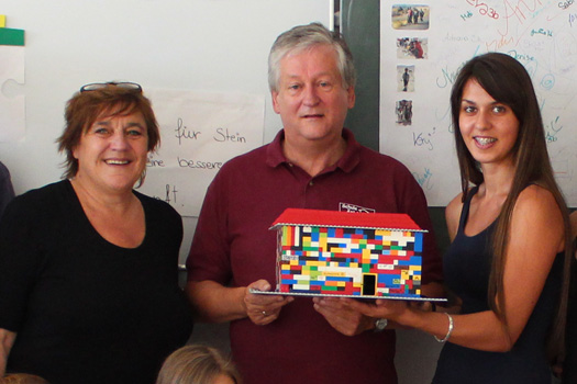 Zwei Frauen und ein Mann mit Legohaus