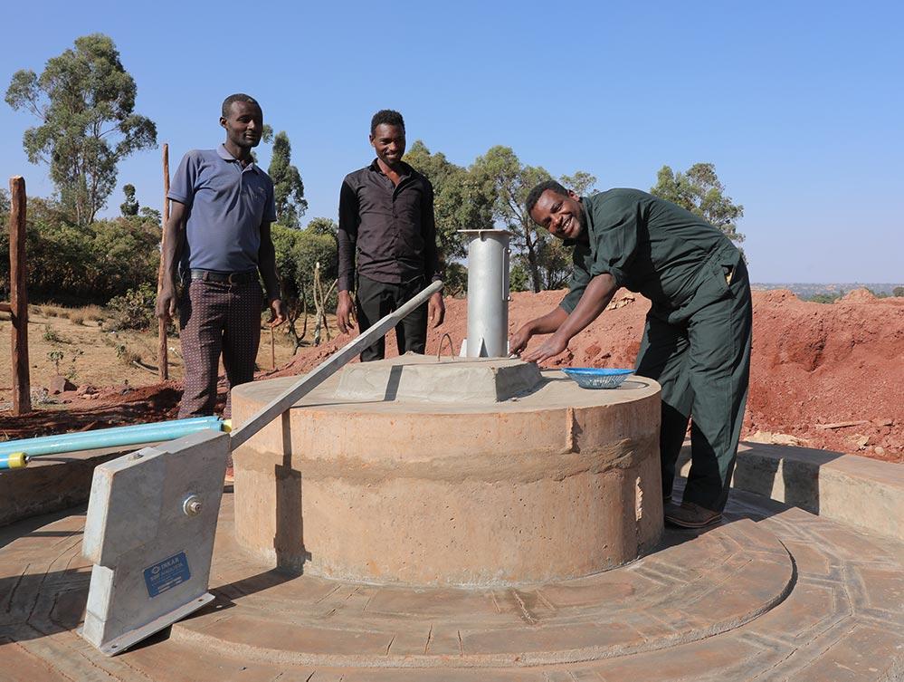 Drei Männer stehen vor einem Brunnen
