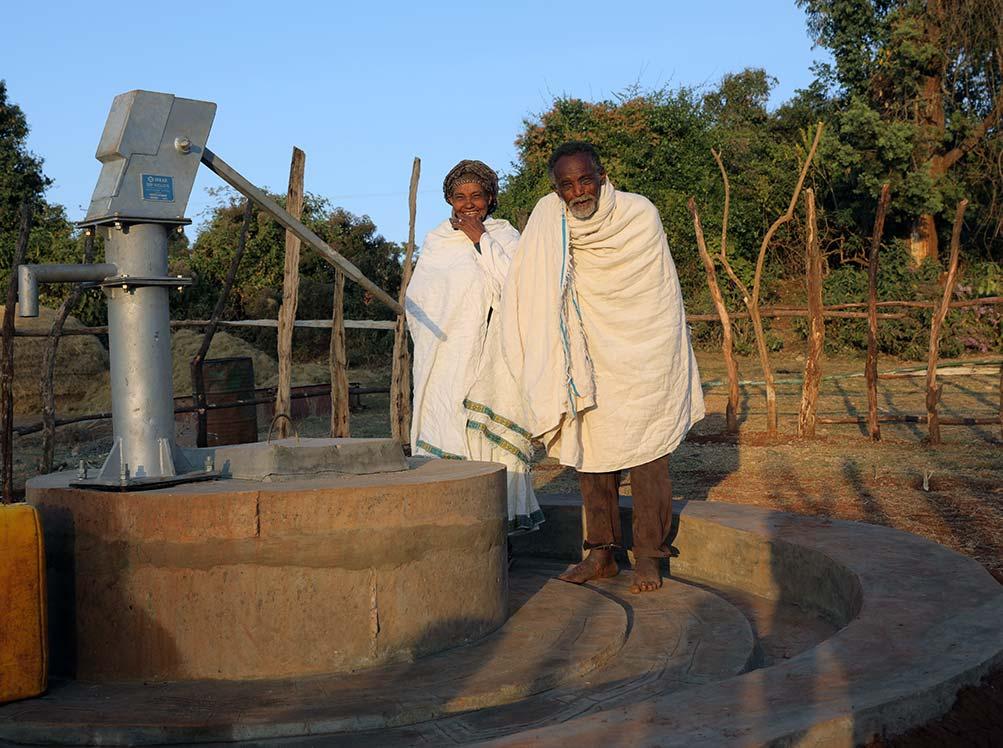 Ein älteres Pärchen steht vor einem Brunnen.