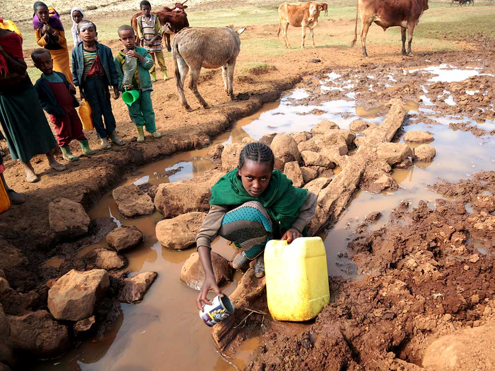 Ein Mädchen holt Wasser aus einer ungeschützten Wasserstelle.