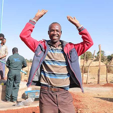 Ein Mann lacht und streckt seine Hände in die Luft.