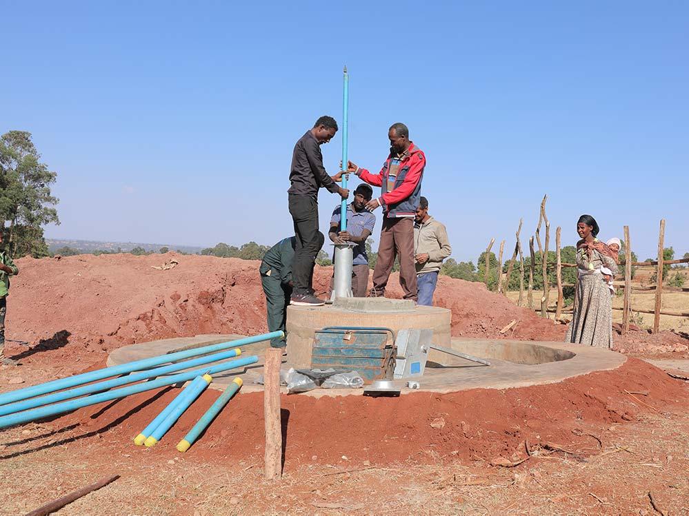 Männer bauen einen Brunnen