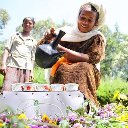 Frau in Äthiopien gießt Kaffee ein