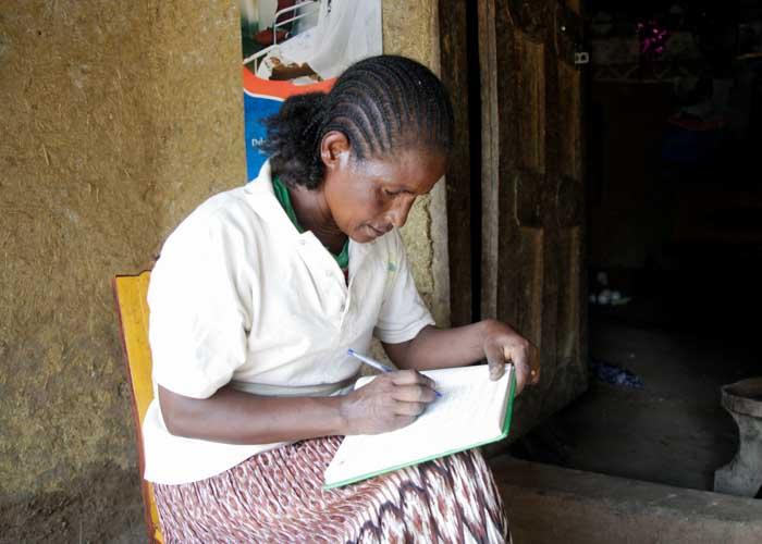 Äthiopische Frau schreibt in ein Buch