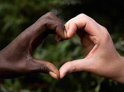 Schwarze und weiße Hand zu einem Herz gefortm