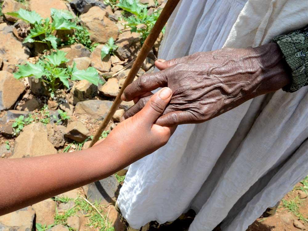 Junge und alte Hand in Äthiopien halten sich