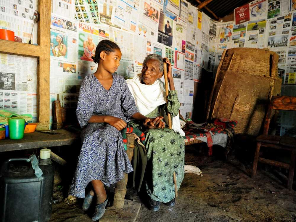 Kind mit fast blinder Oma sitzen in ihrer Hütte in Äthiopien