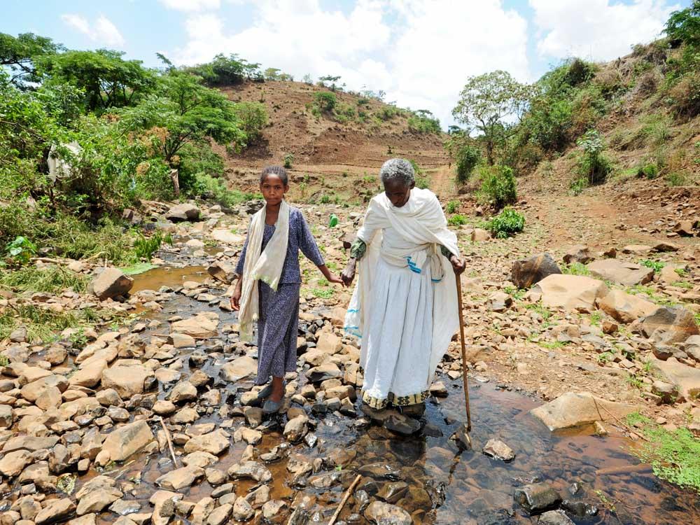 Kind führt fast blinde Oma durch einen Fluss an der Hand