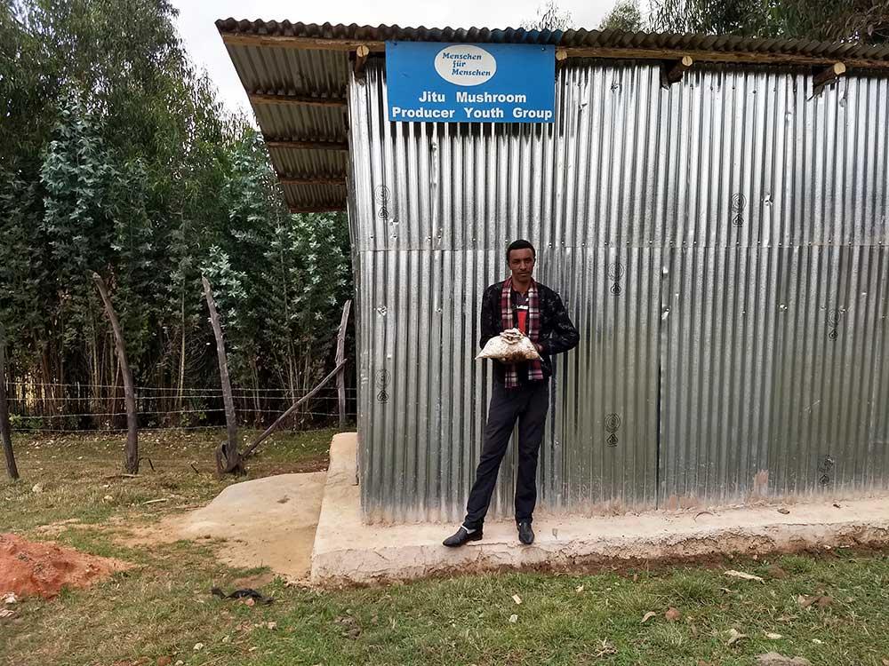 Ein Mann steht vpr einem Gebäude.