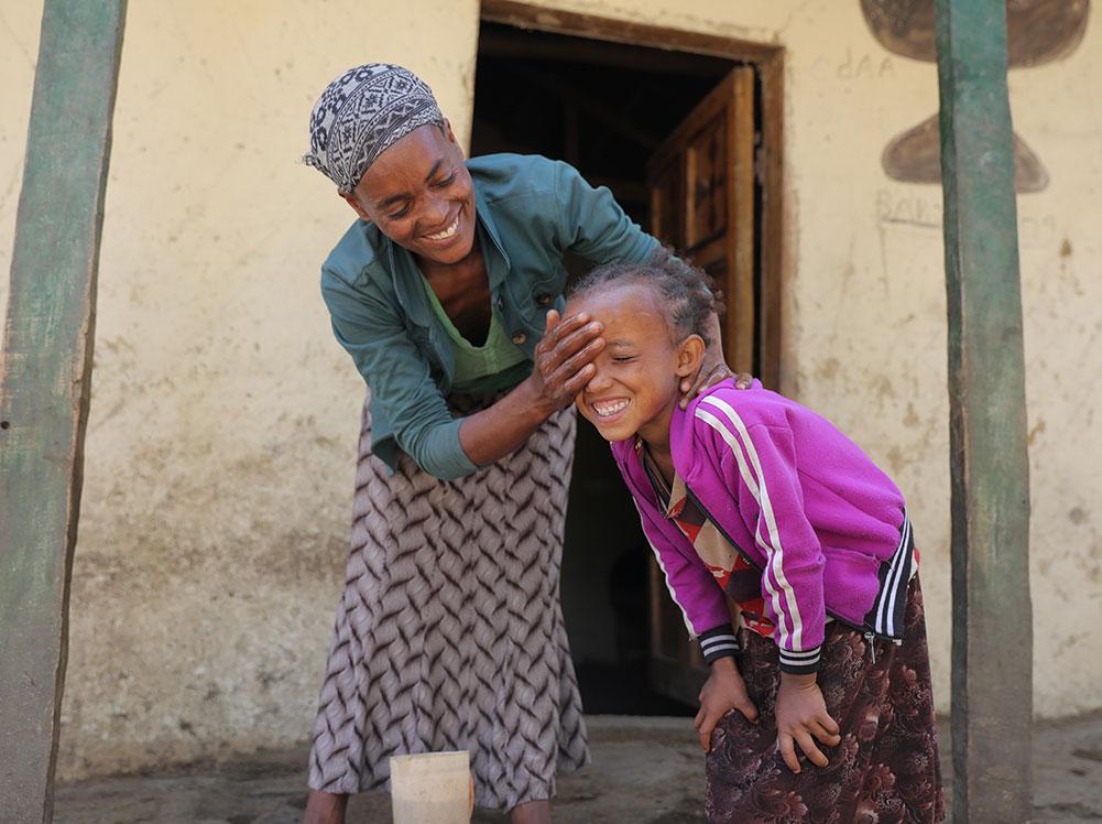 Eine Mutter wäscht ihrem Kind das Gesicht.