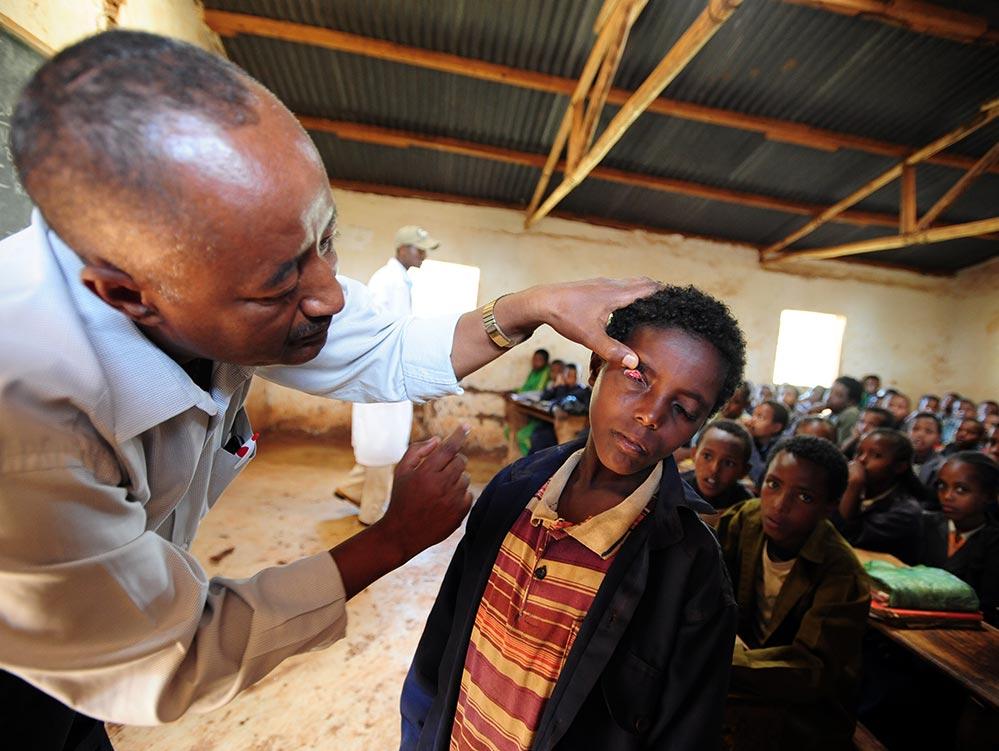 Ein Arzt untersucht ein Kind in einem Klassenzimmer.