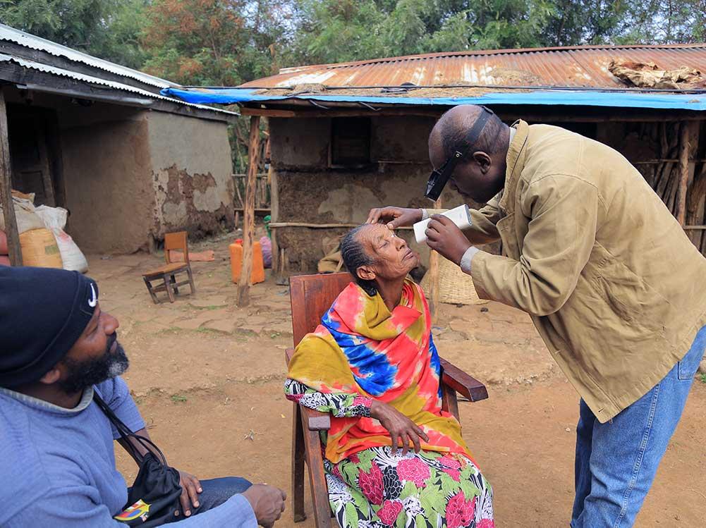 Ein Mann untersucht eine ältere Dame.