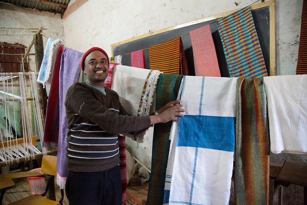 Ein Mann zeigt auf bunte Tücher.