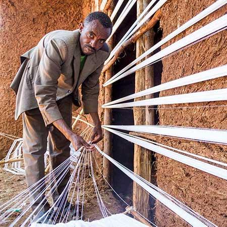 Ein Mann spannt Fäden.