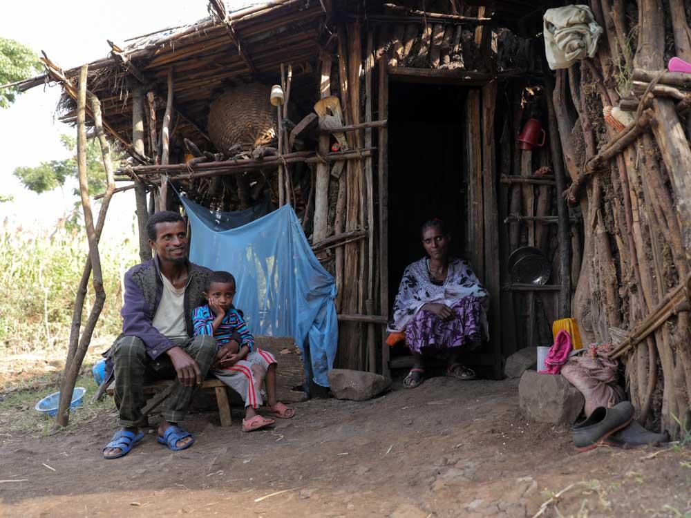 Äthiopische Familie vor ihrer Holzhütte