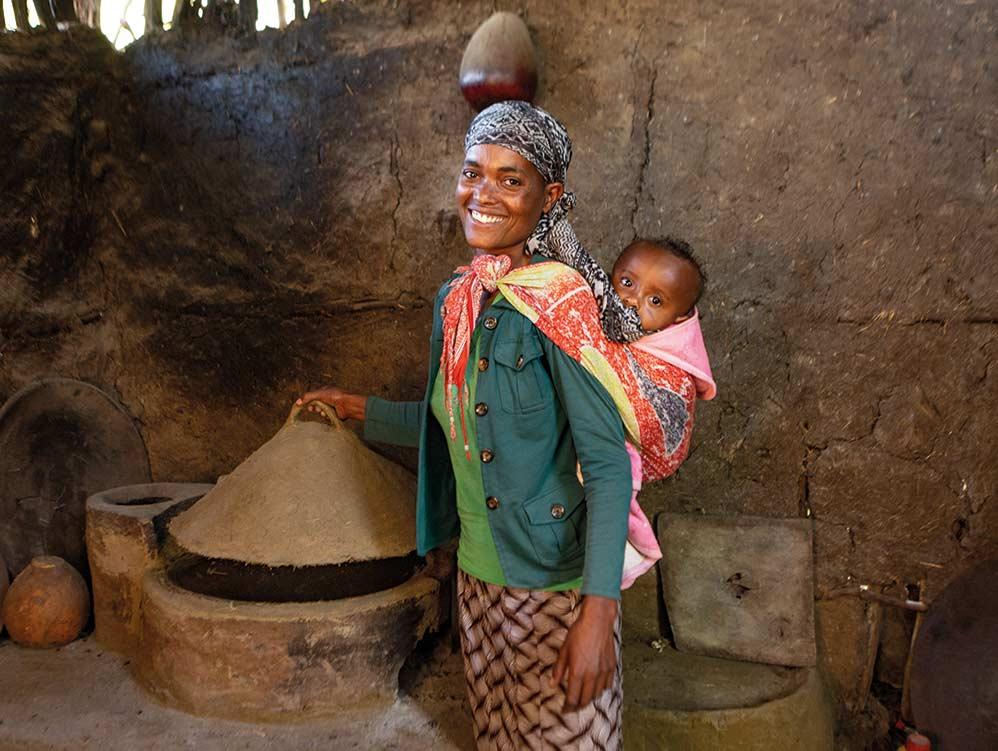 Frau in Äthiopien mit Kind auf ihrem Rücken bei einem holzsparenden Ofen