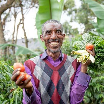 Grinsender Äthiopischer Mann mit Gemüse in der Hand