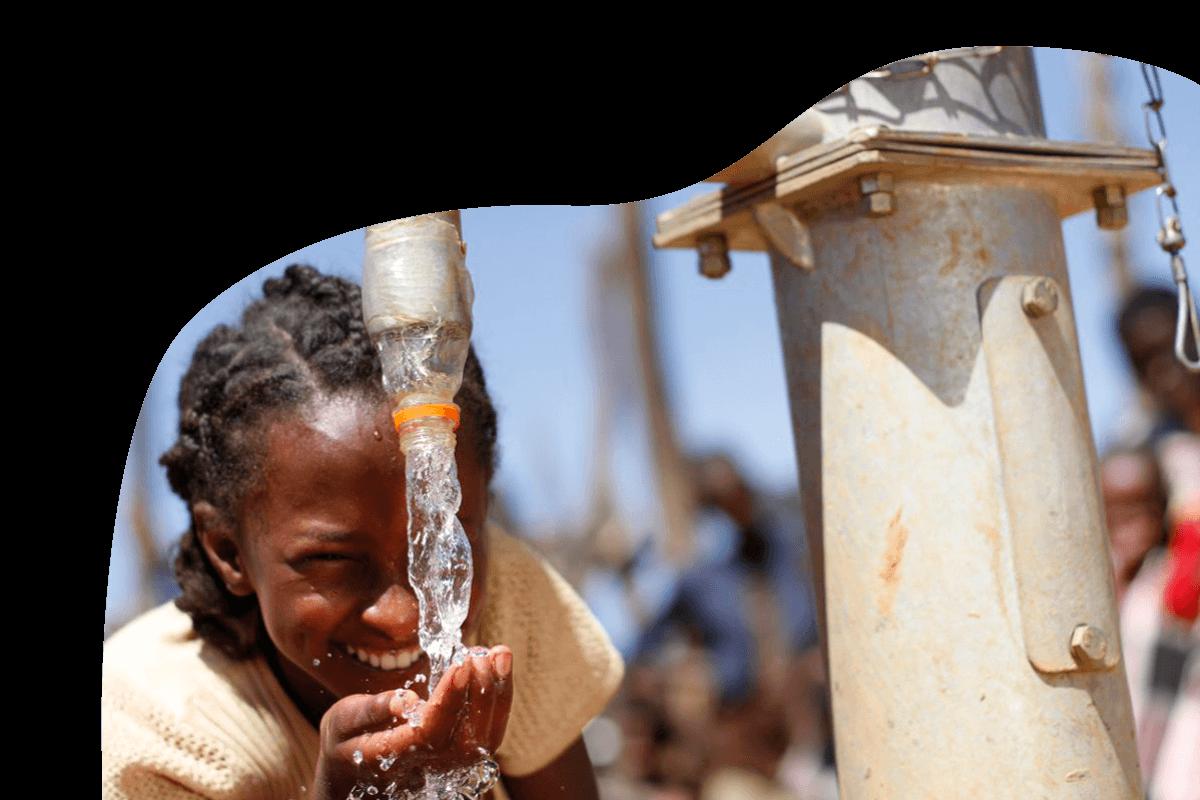 Mädchen trinkt von Wasserquelle und lächelt