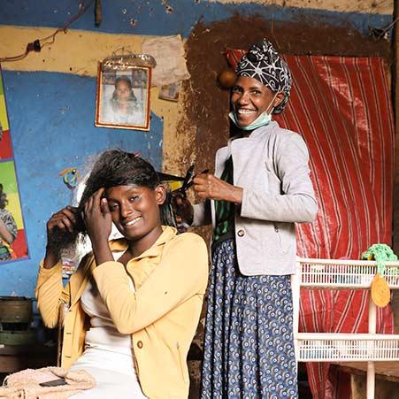 Friseurin in Äthiopien schneidet Haare einer Kundin