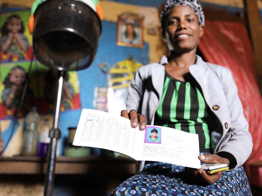 Friseurin in Äthiopien zeigt Buch ihrer Kreditgruppe