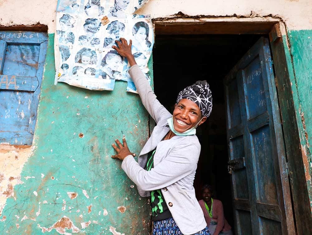 Friseurin in Äthiopien steht vor ihrem laden und hängt Werbung auf