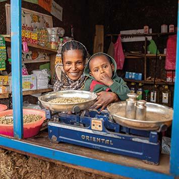 Frau mit Kind sitzt in ihrem Geschäft in Äthiopien vor einer Waage