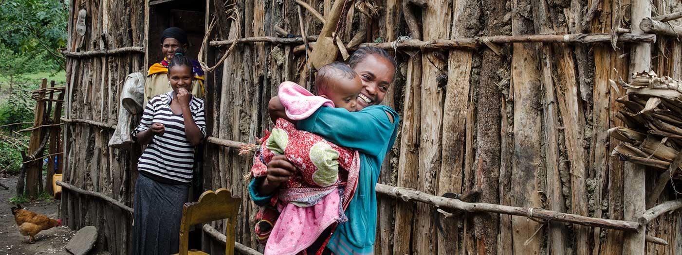 Frau mit ihrem kleinen baby im arm in Äthiopien vor einer Holzhütte