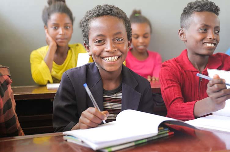 Schüler in Äthiopien grinst über seinem Buch