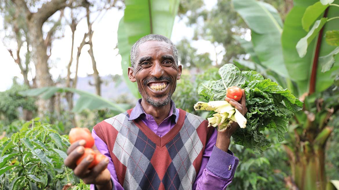 Mann in Äthiopien grinst und hält Obst und Gemüse in den Händen