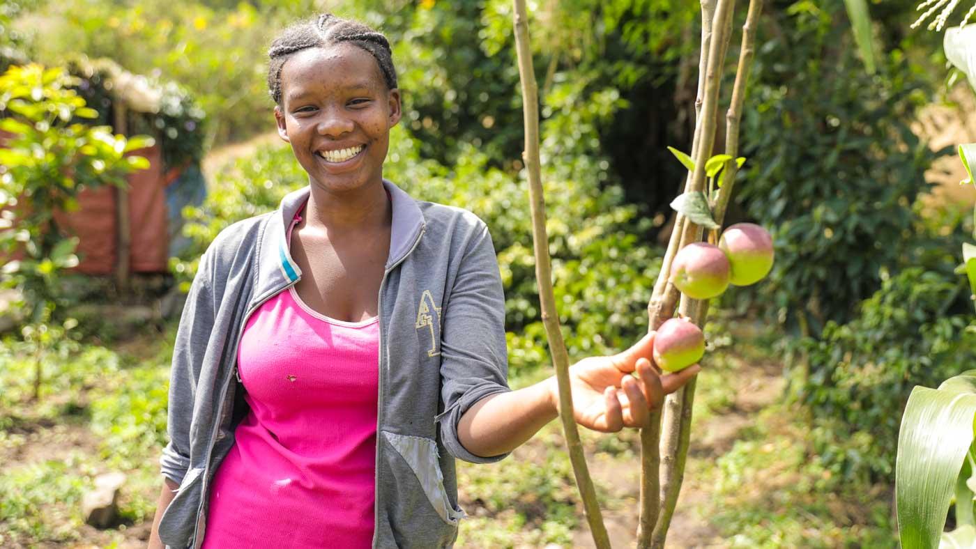 Junge Frau in Äthiopien steht bei einem Apfelbaum