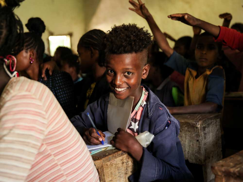 Junge in einer dunklen äthiopischen Schule lacht