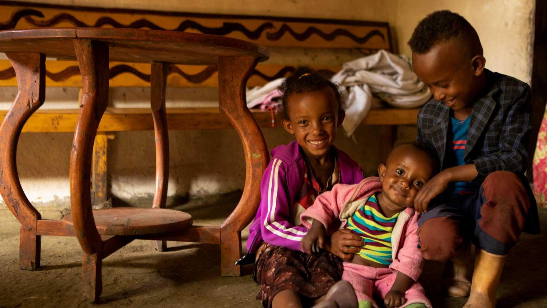 Drei kleine Kinder in Äthiopien sitzen in ihrer Hütte