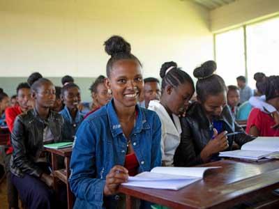 Äthiopisches Mädchen sitzt lächelnd in der Schulklasse