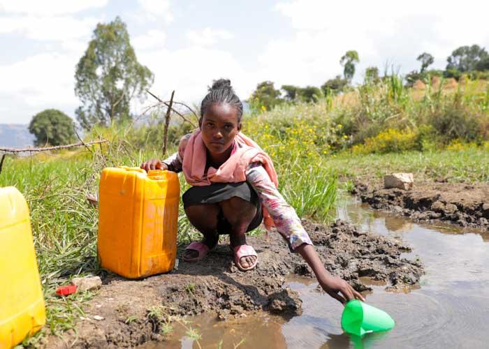Mädchen in Äthiopien schöpft Wasser aus einer Pfütze