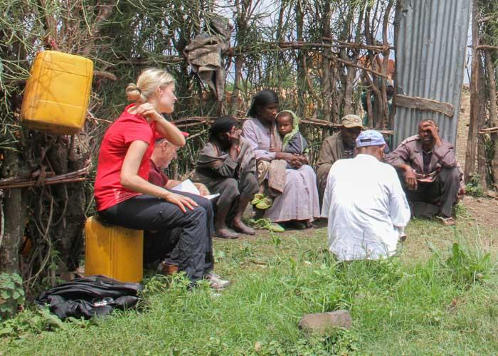Weisse Frau sitzt in Äthiopien in einer Gruppe von Menschen
