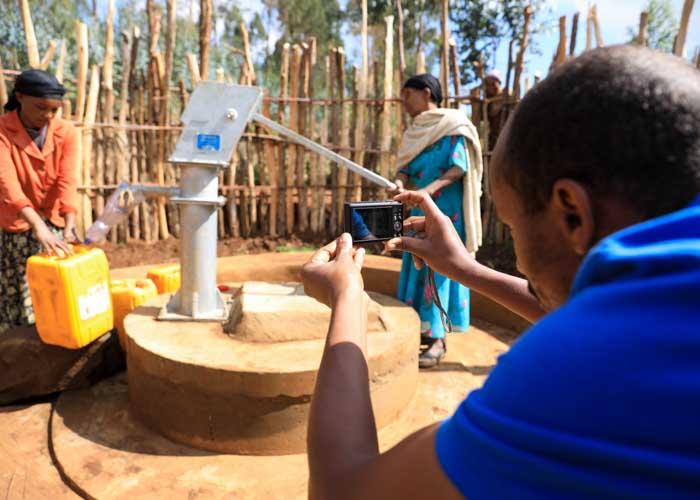 Mitarbeiter von menschen für menschen macht Foto von einem neuen Brunnen