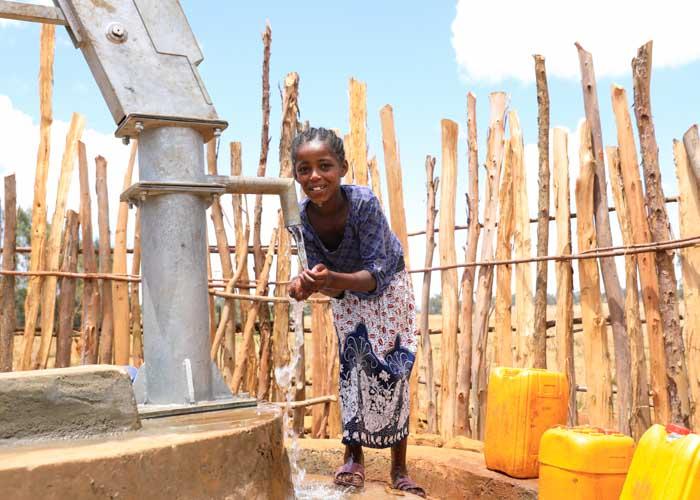 Mädchen in Äthiopien holt Wasser von einem neuen Brunnen