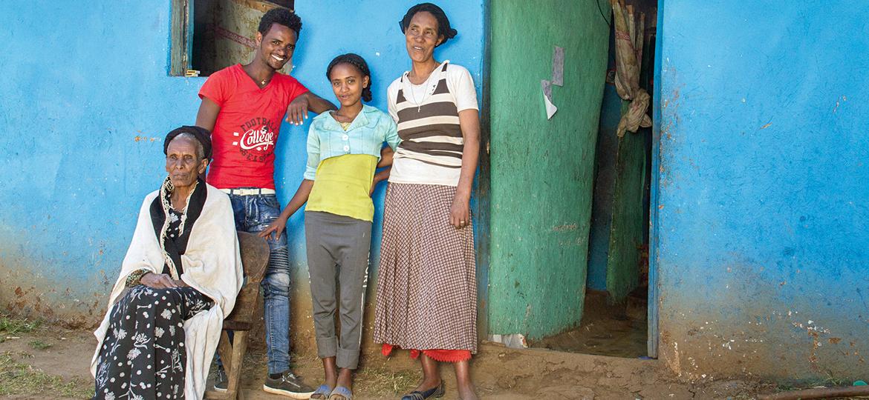 Eine Familie steht vor einem Haus.